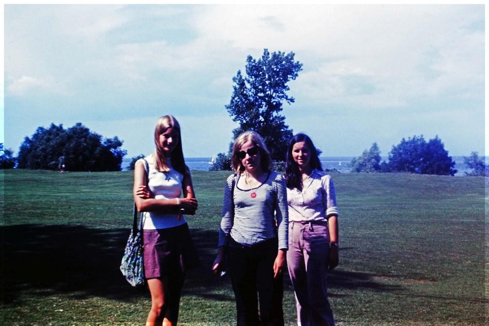 Three teenage girls on a lawn by a lake