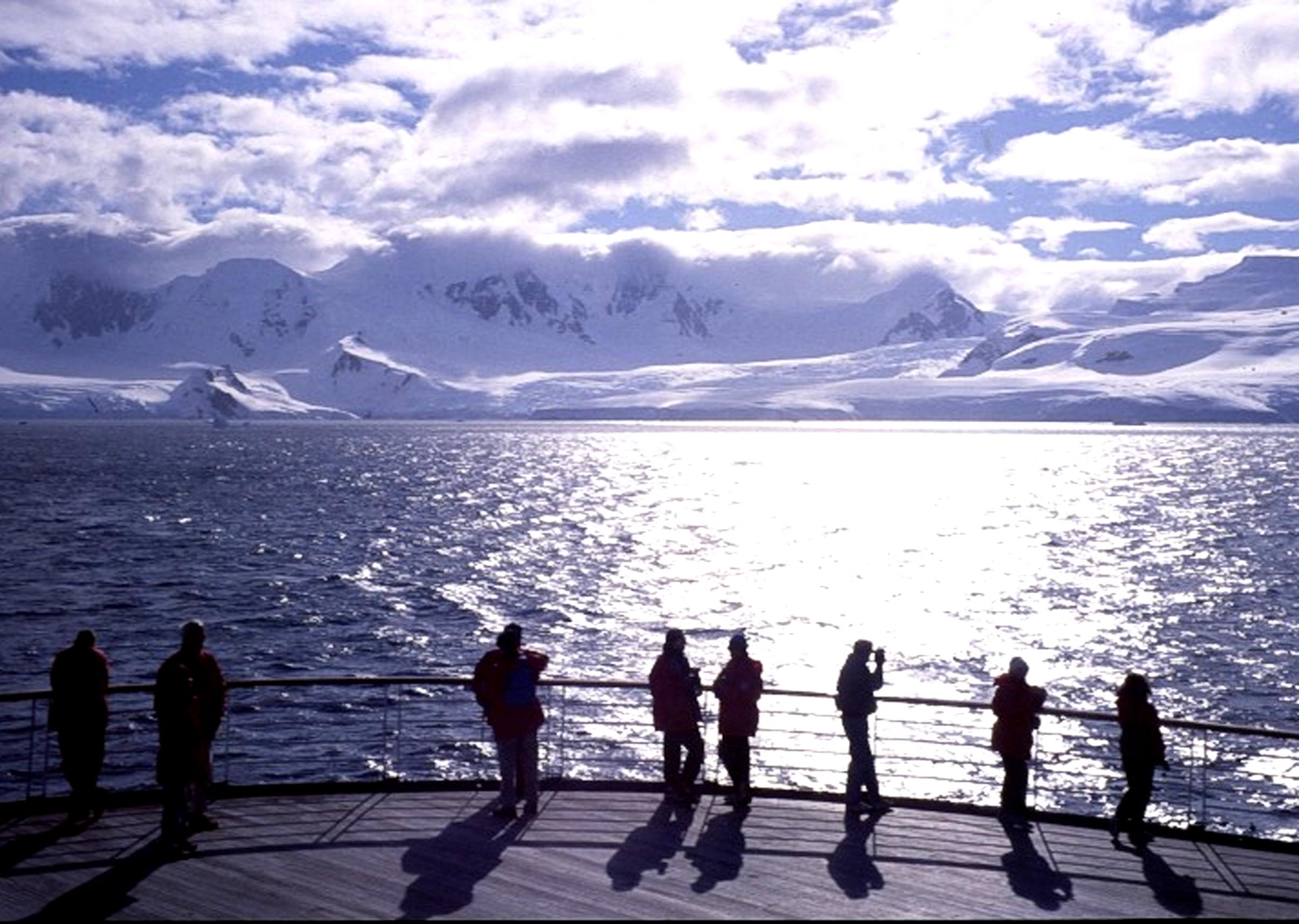People on the deck of a ship looking at snowy coastline