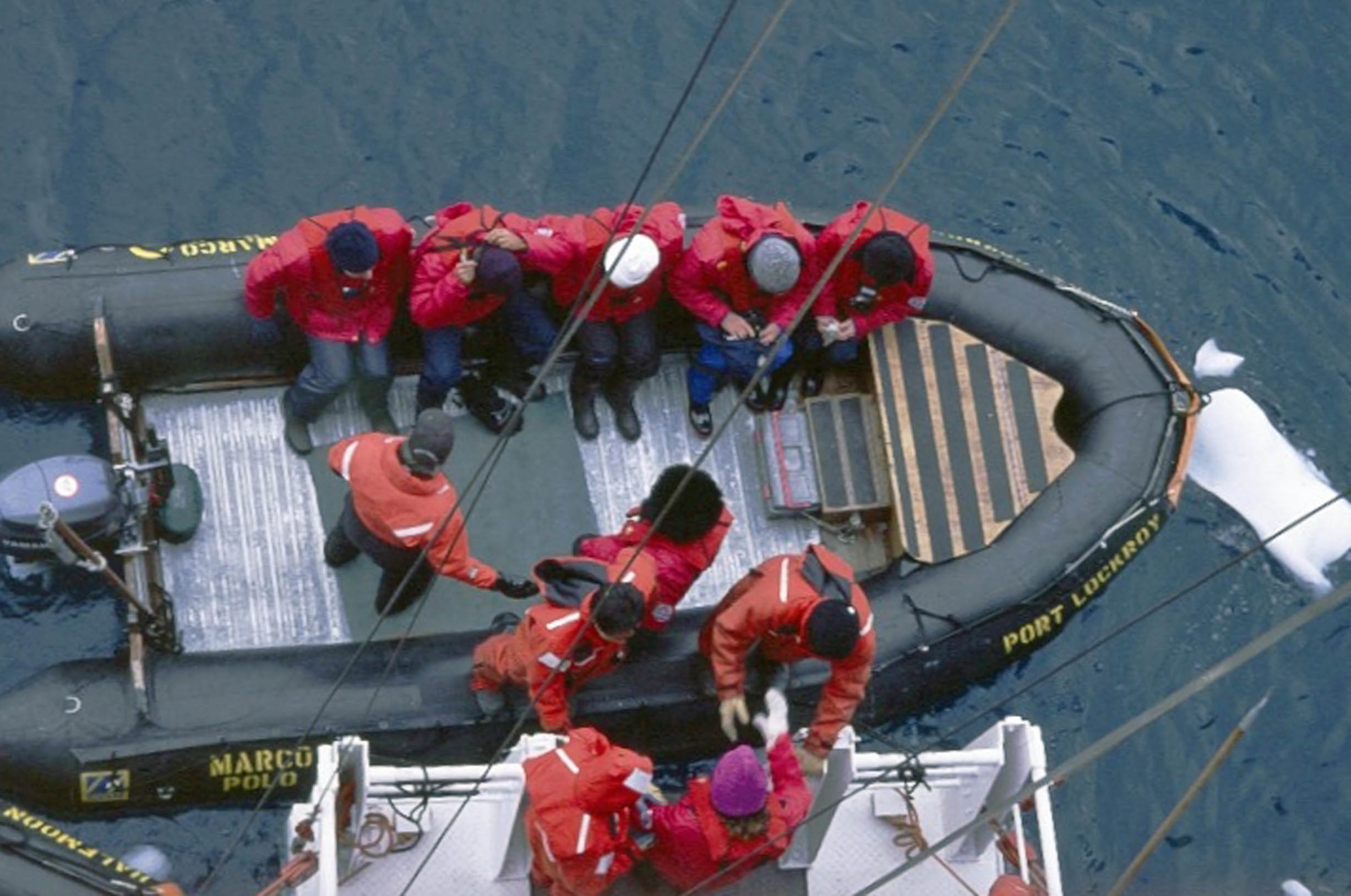 People in red anoraks on a small boat, seen from above