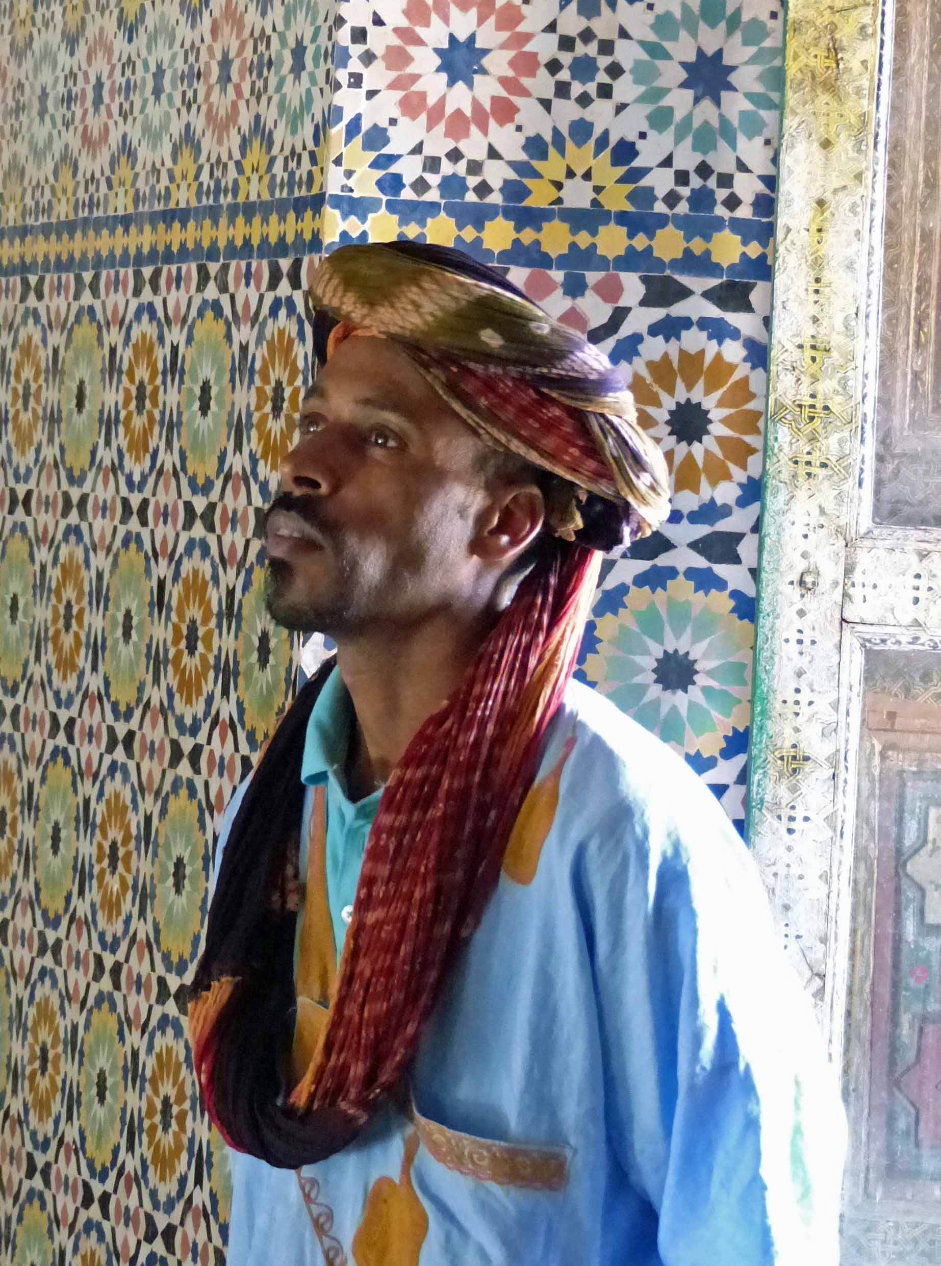 Man in blue robes in tiled room