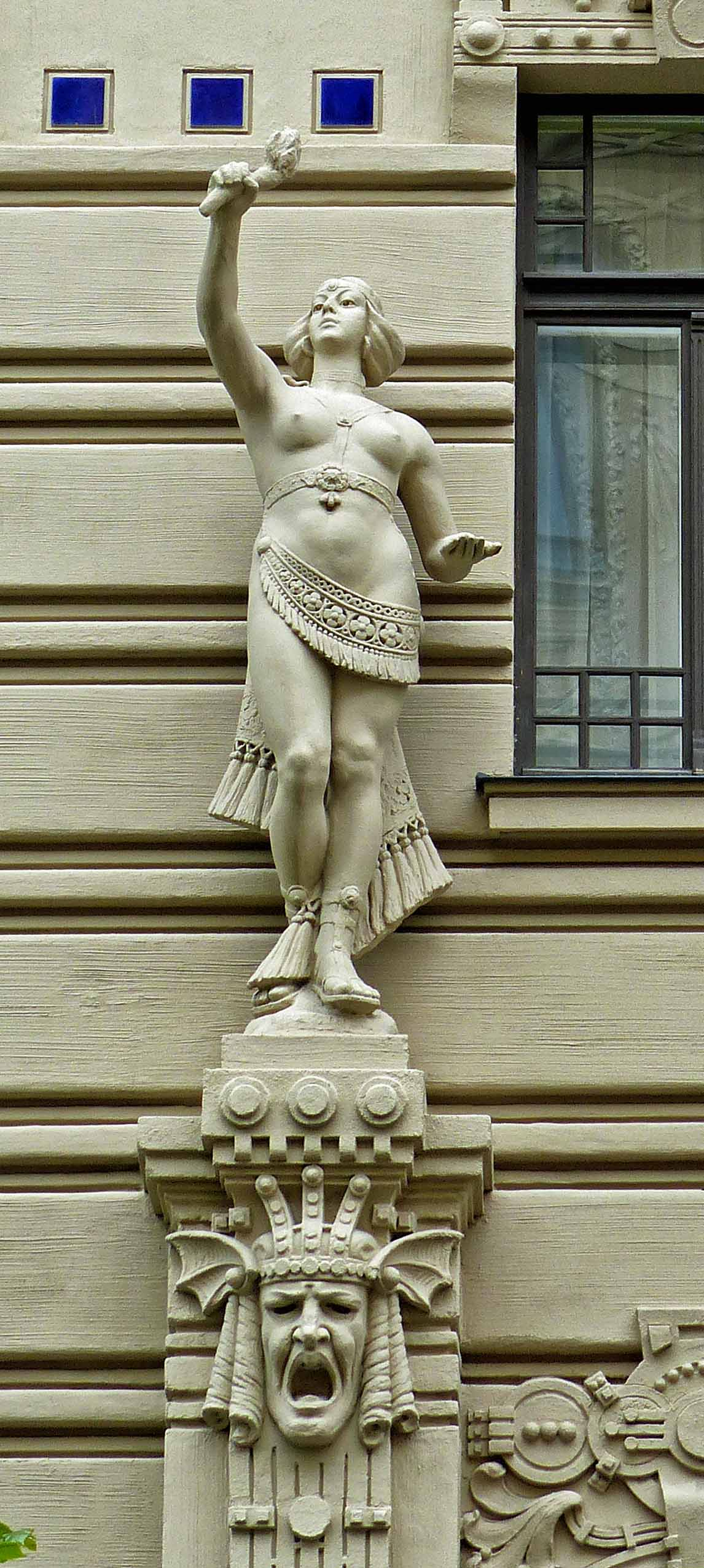 Carving of a stone figure holding a torch on the front of a building