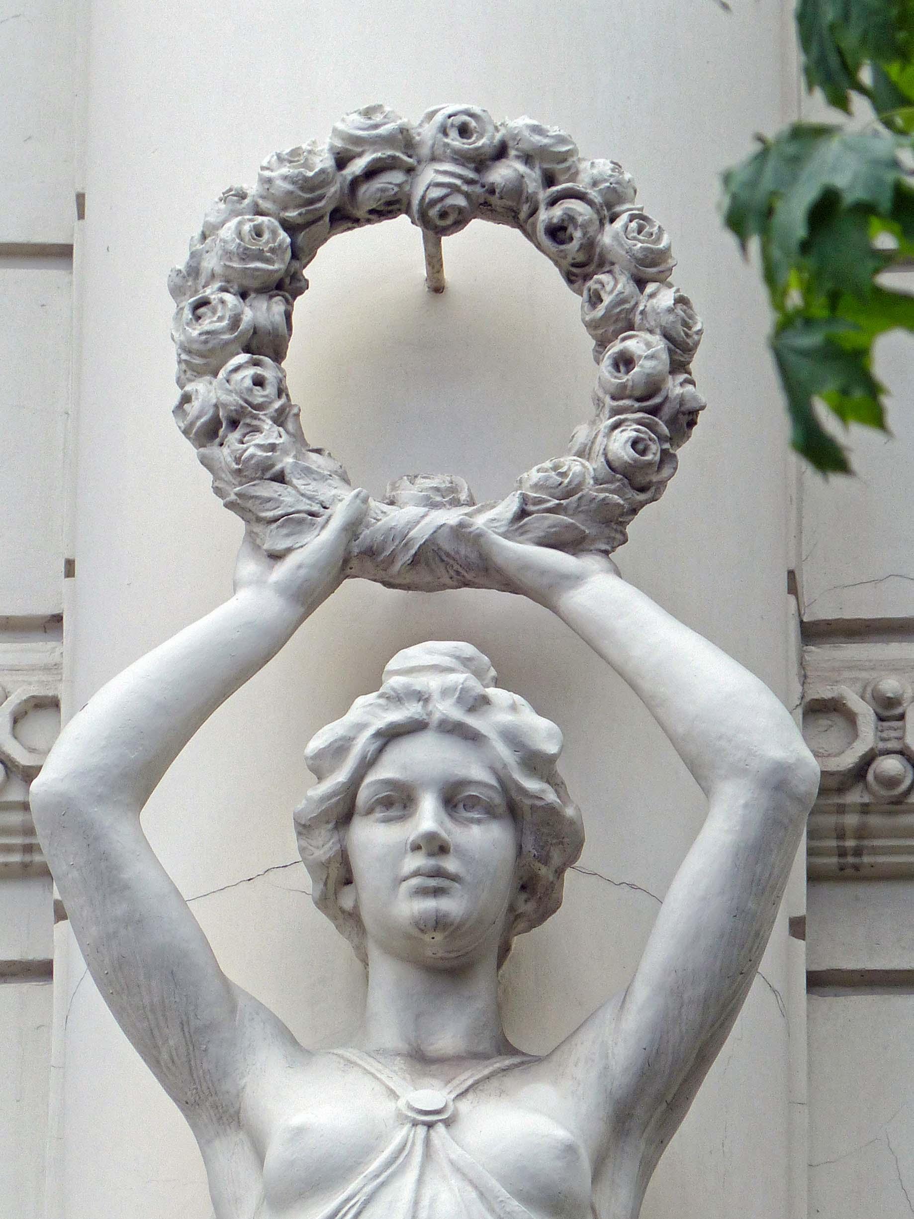 Stone female figure holding a wreath