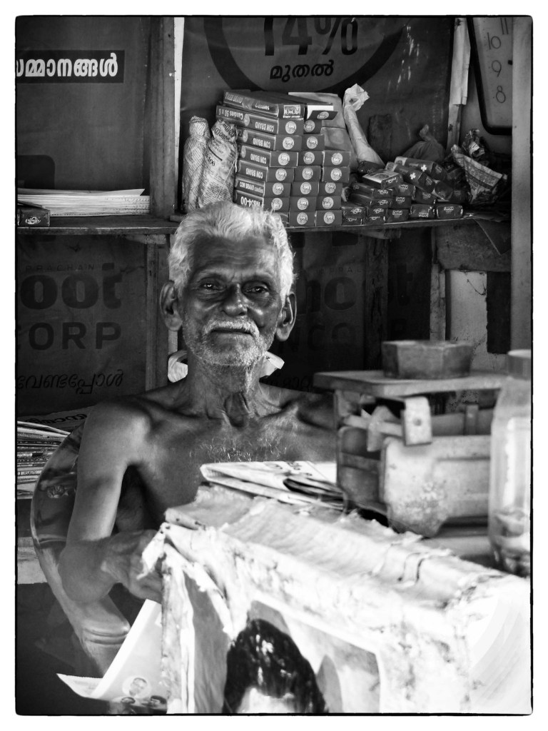 Black and white photo of man in a simple shop