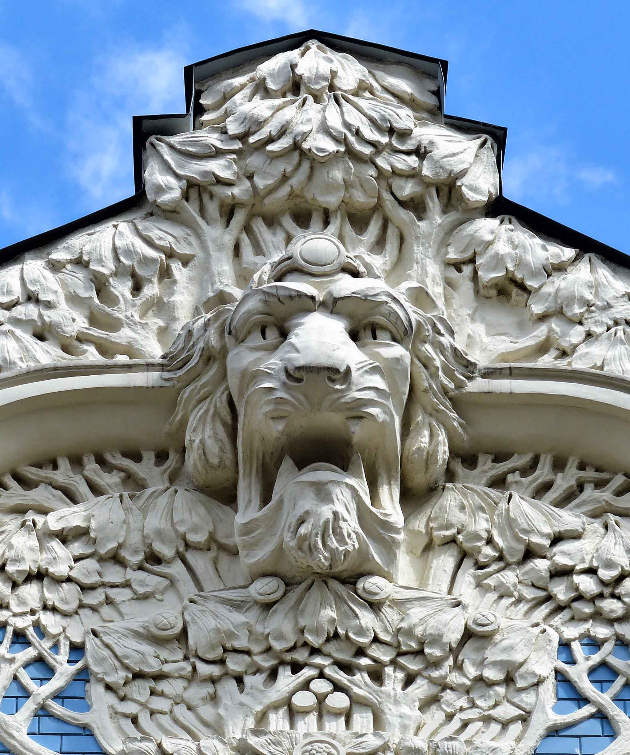 Fierce lion face carved in white stone on a building