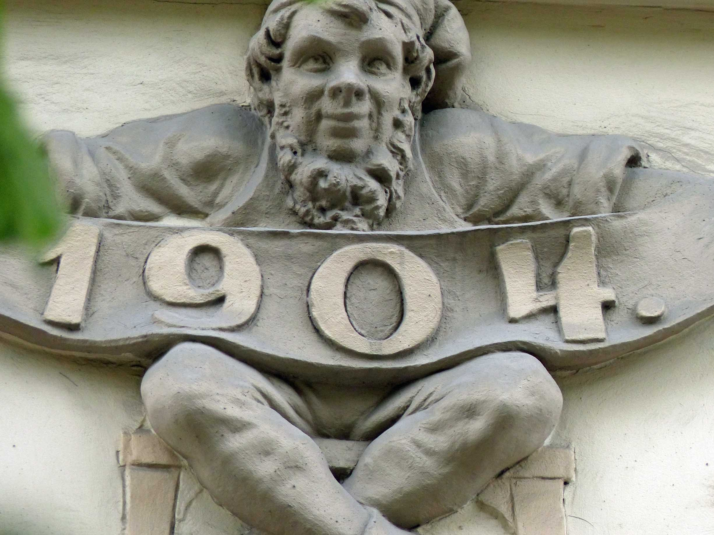 Gnome-like carved figure holding banner with date 1904