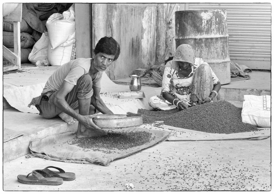Black and white photo of two people sifting grain