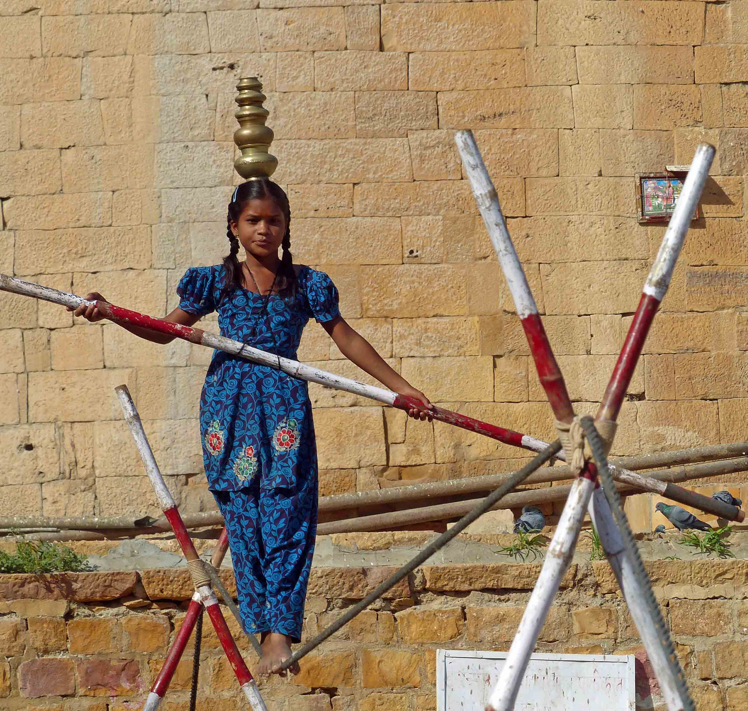 Girl in blue tunic balancing on a tightrope
