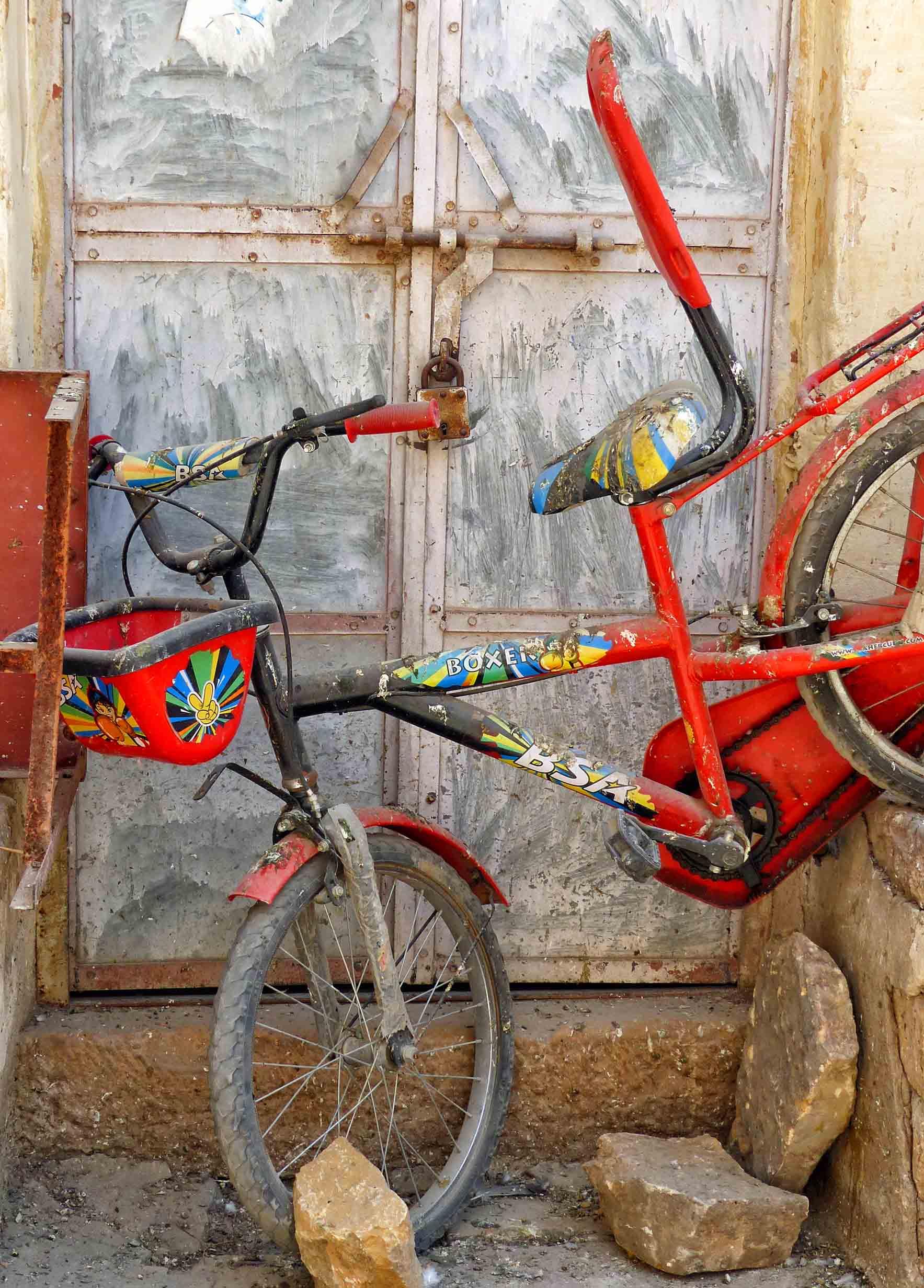 Brightly coloured bike in front of door