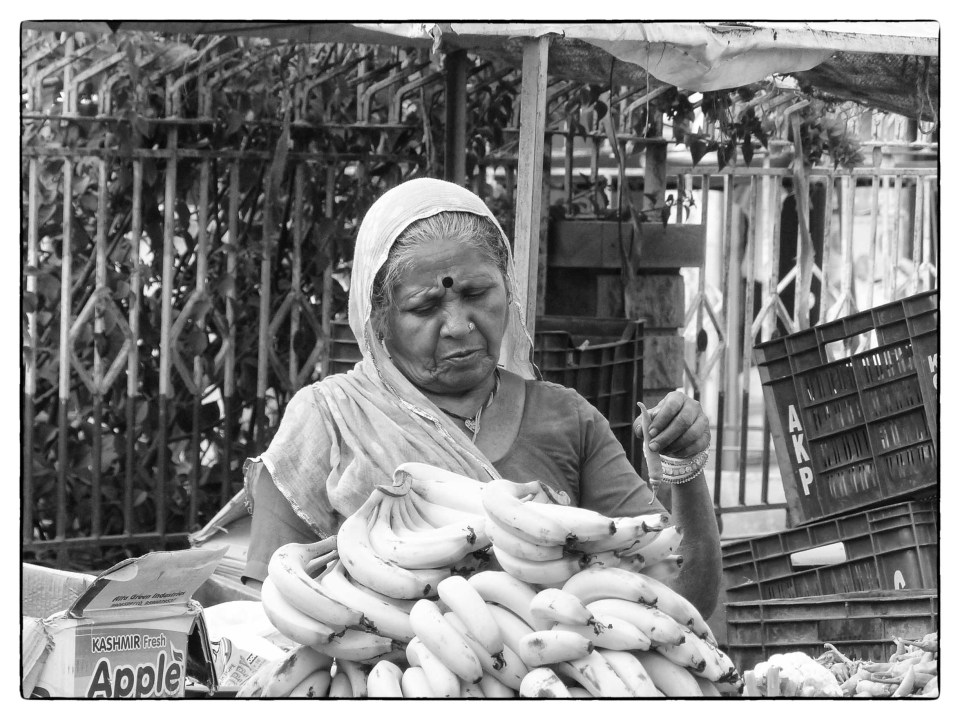 Black and white photo of lady at a stall of bananas