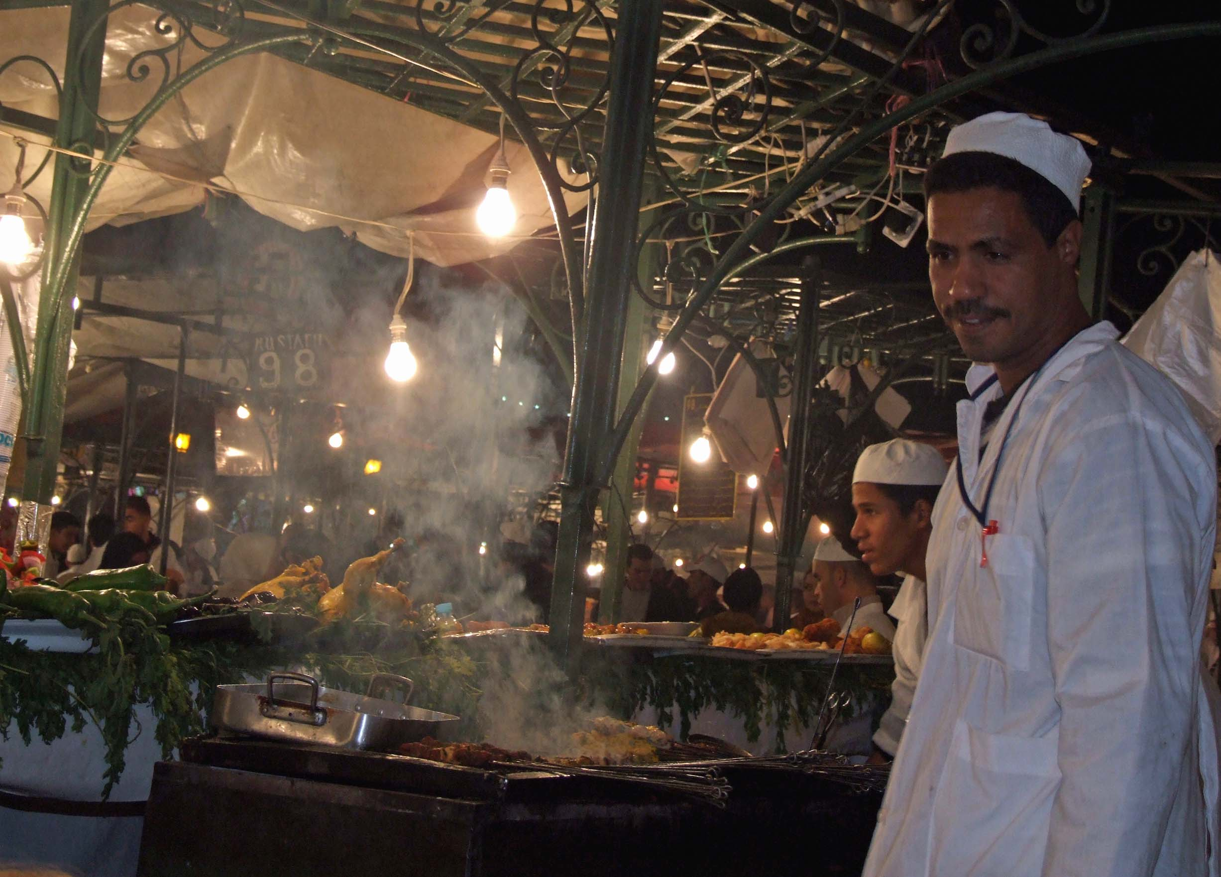 Men in white cooking on open grills