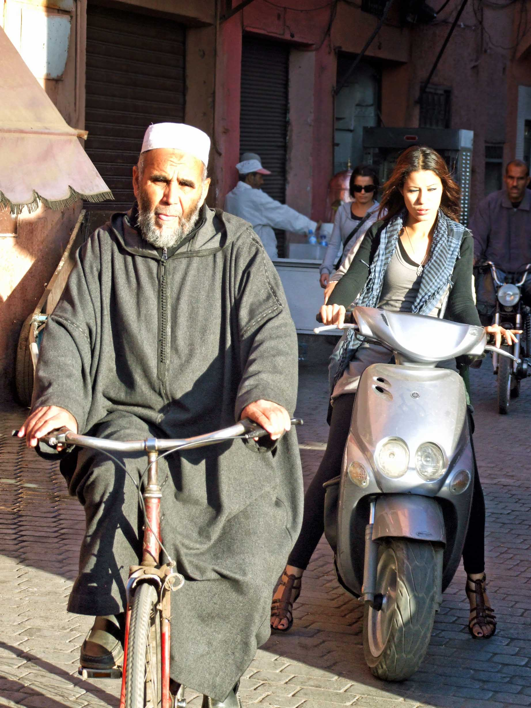 Man in traditional robe on a bicycle and young lady in modern dress on a moped