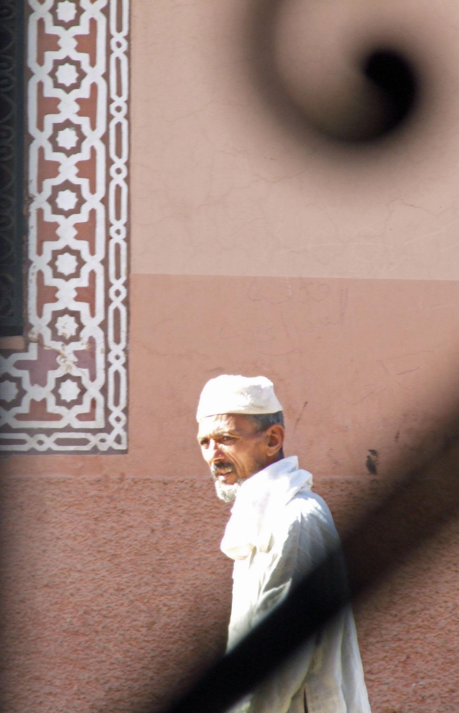 Man in white robe seen through ornate railing