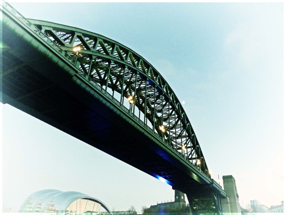 Looking up at large arching bridge