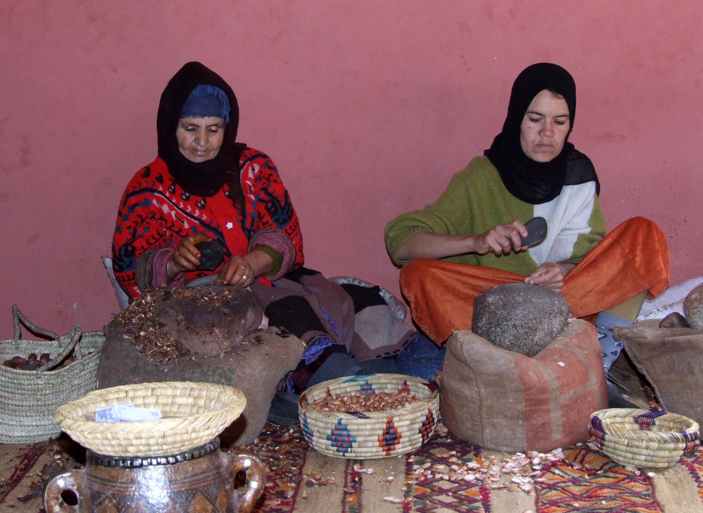 Two women seated and pounding nuts with stones