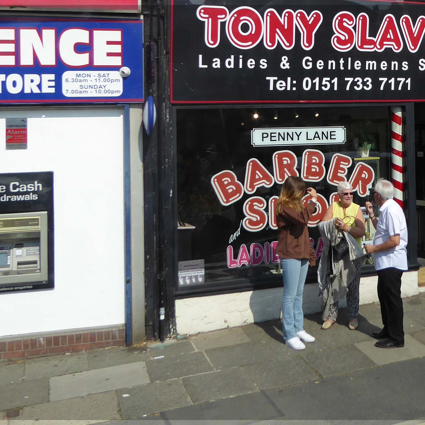 Street with barber's shop and cash machine, people talking outside
