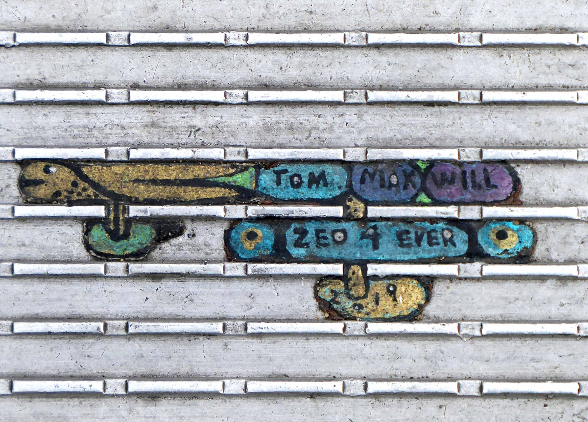 Tiny multi-coloured painting on ridged metal surface