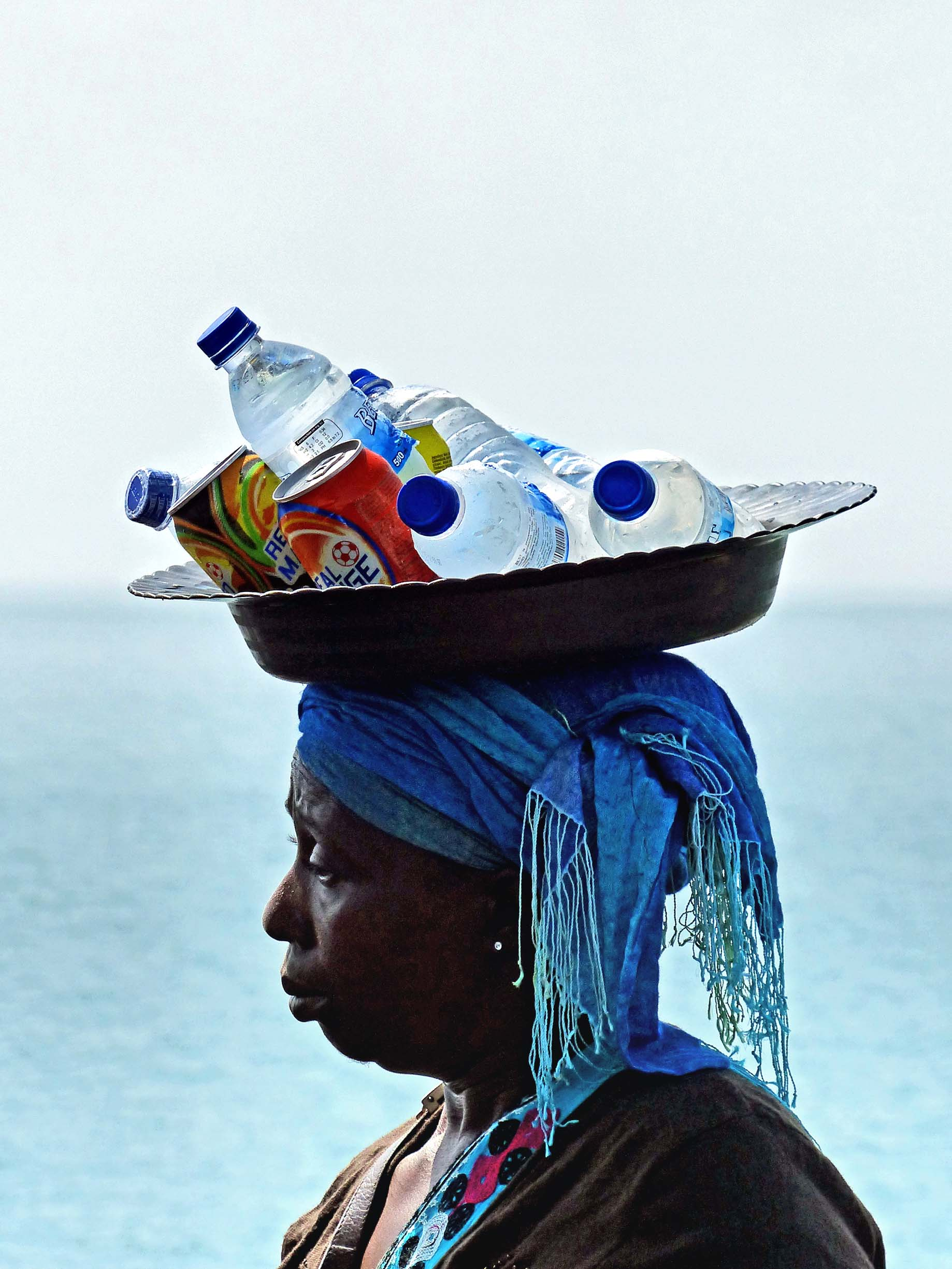 Lady with tray of drinks bottles and cans on her head