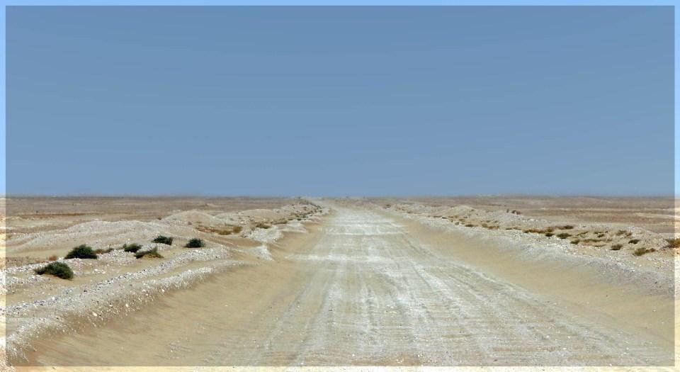 Gravel road across flat plain