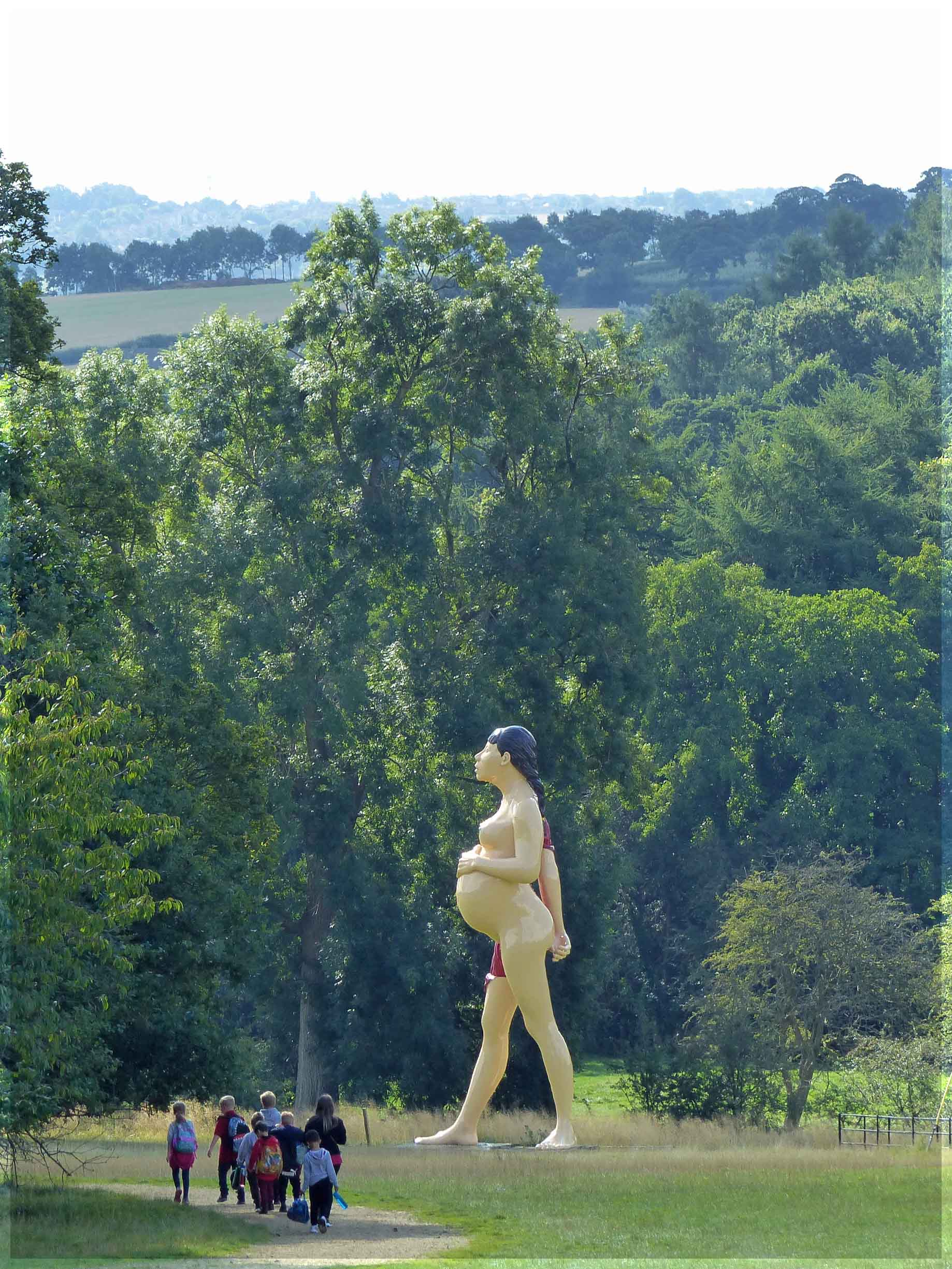 Huge sculpture of pregnant woman with group of children walking past