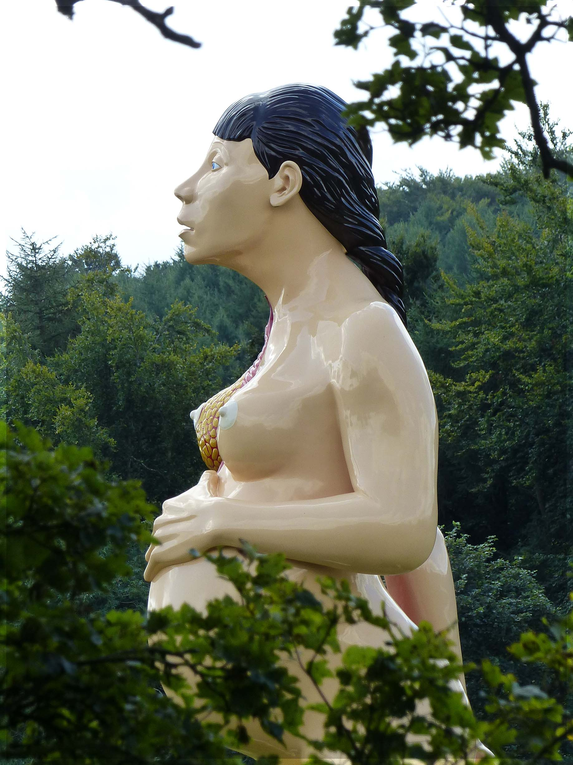 Huge sculpture of pregnant woman seen above trees