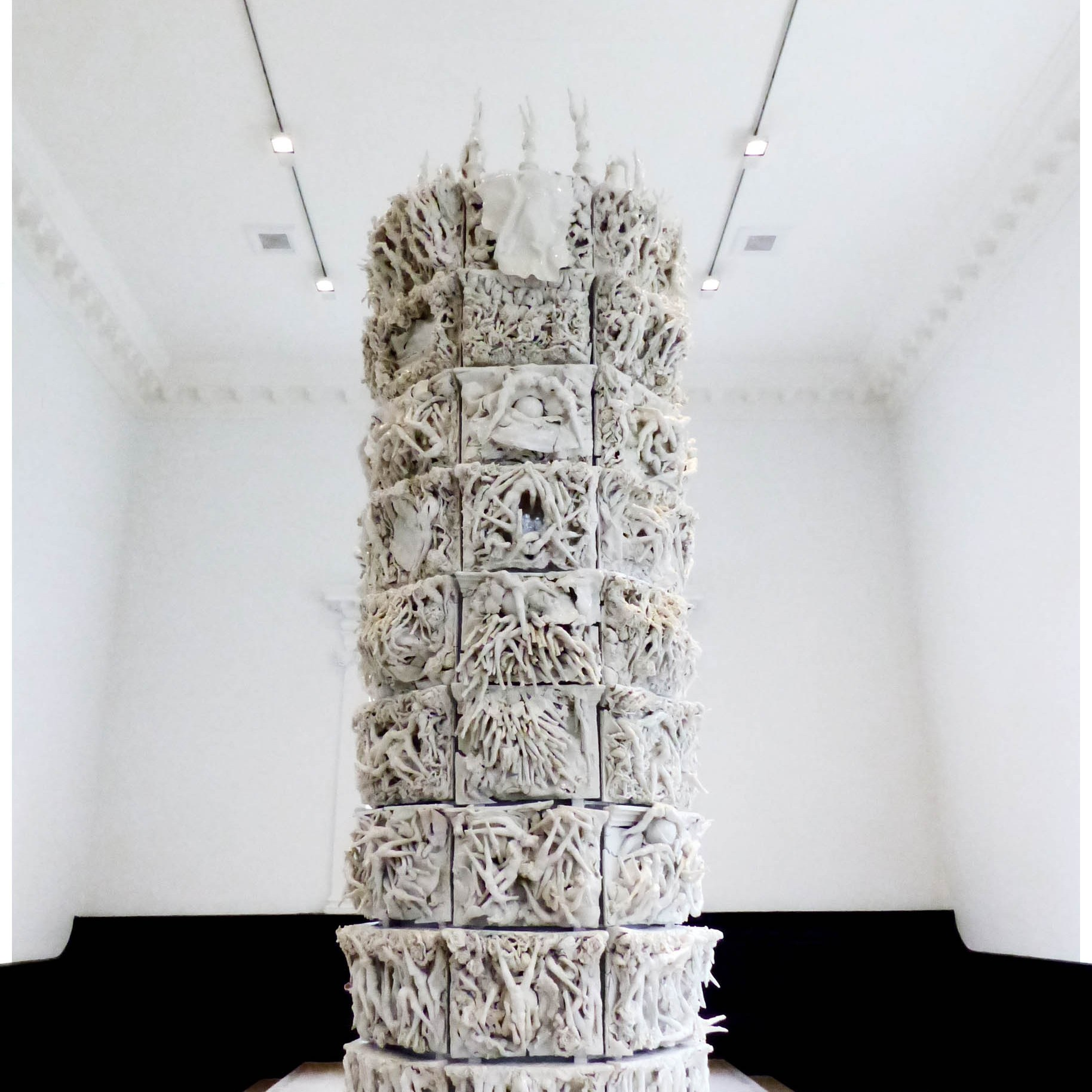 Tall column ceramic white sculpture with many legs and flowers entwined