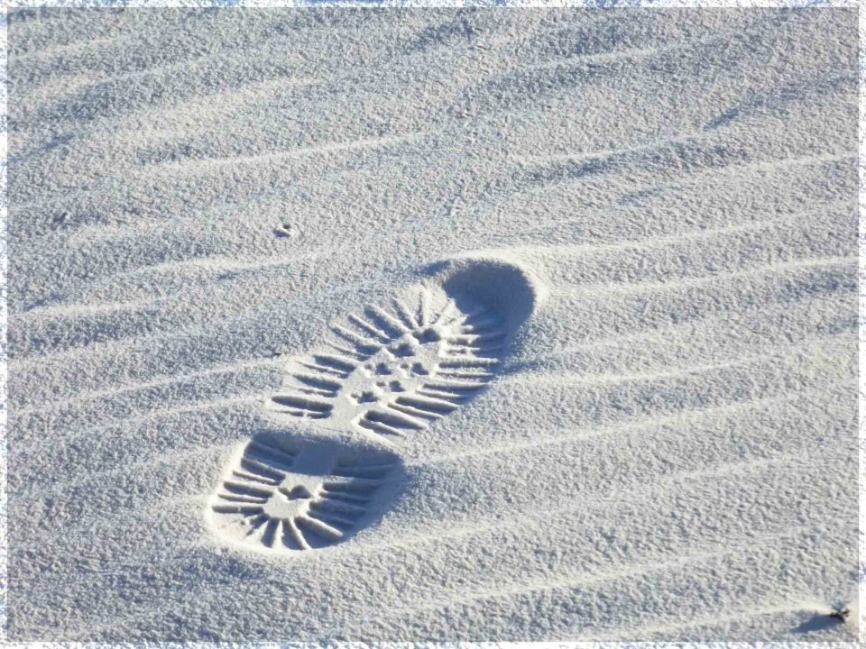 Imprint of a shoe on white sand