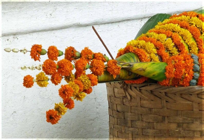 Basket with small offering made of marigold flowers and banana leaves