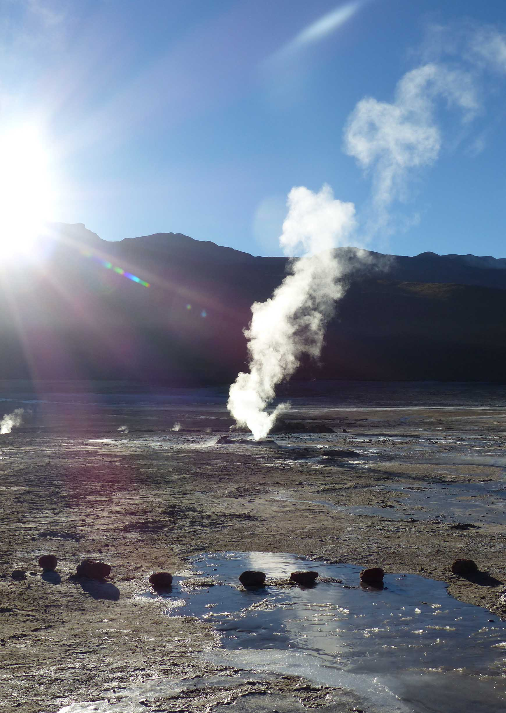 Steam rising from a geyser with sun burst
