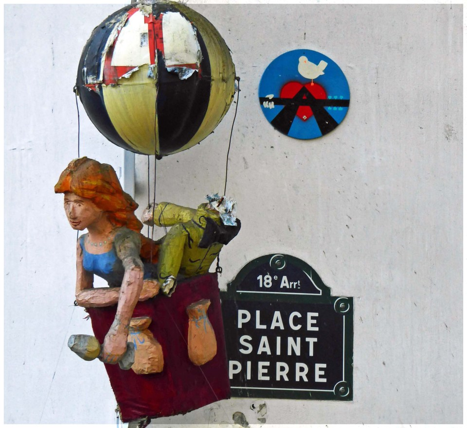 Little model of a girl in a balloon and a red heart on a blue disc