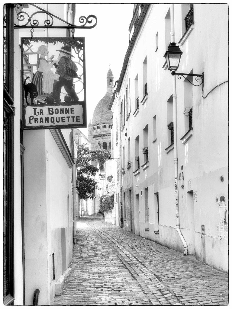 Black and white photo of cobbled street with cafe sign