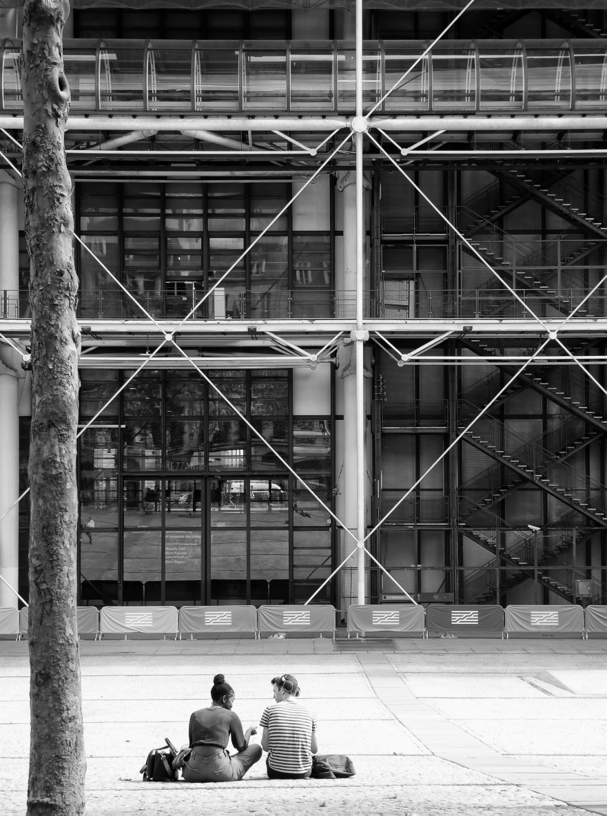 Black and white photo of two young people sitting outside a modern building