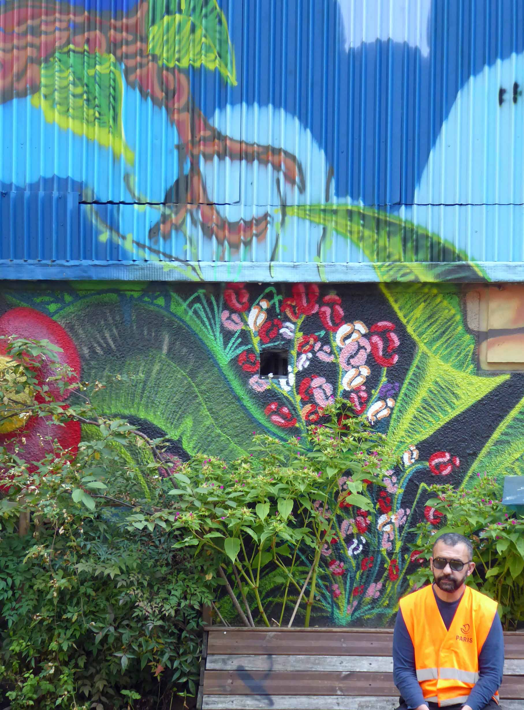 Mural of jungle with man on bench in front