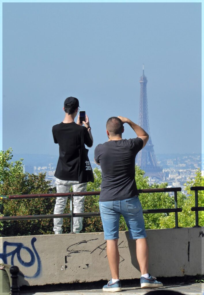 Two men photographing a distant tower