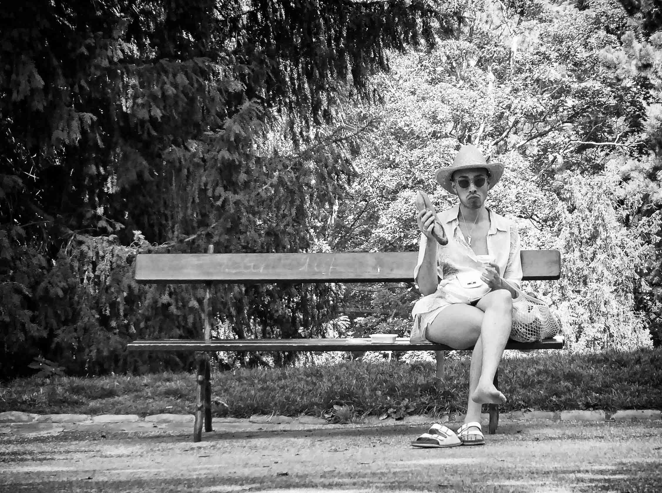 Black and white photo of a man on a bench