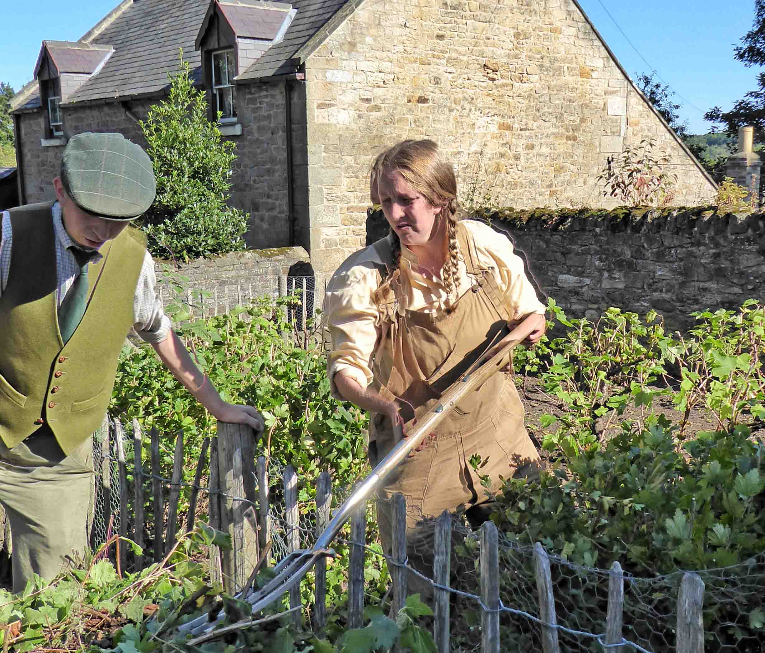Girl in brown overalls with a garden fork