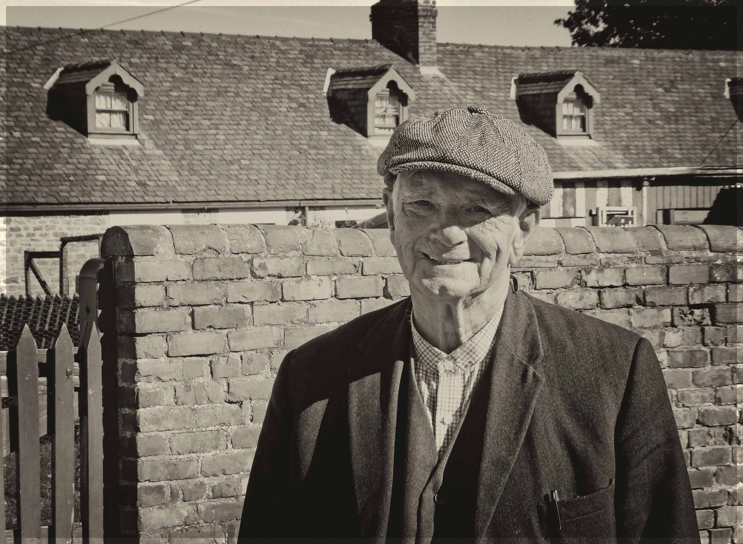 Sepia photof of a man in cloth cap in front of row of cottages