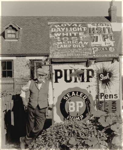 Sepia photo of man in a garden with a shed built from old signs