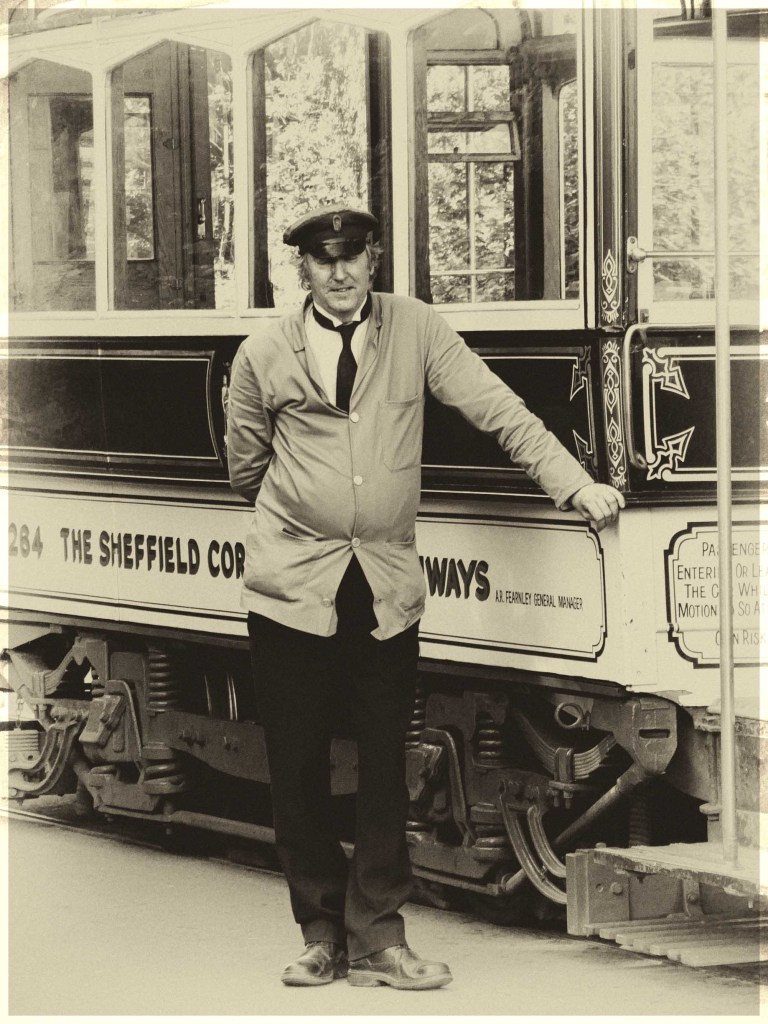 Sepia photo of man standing by a tram