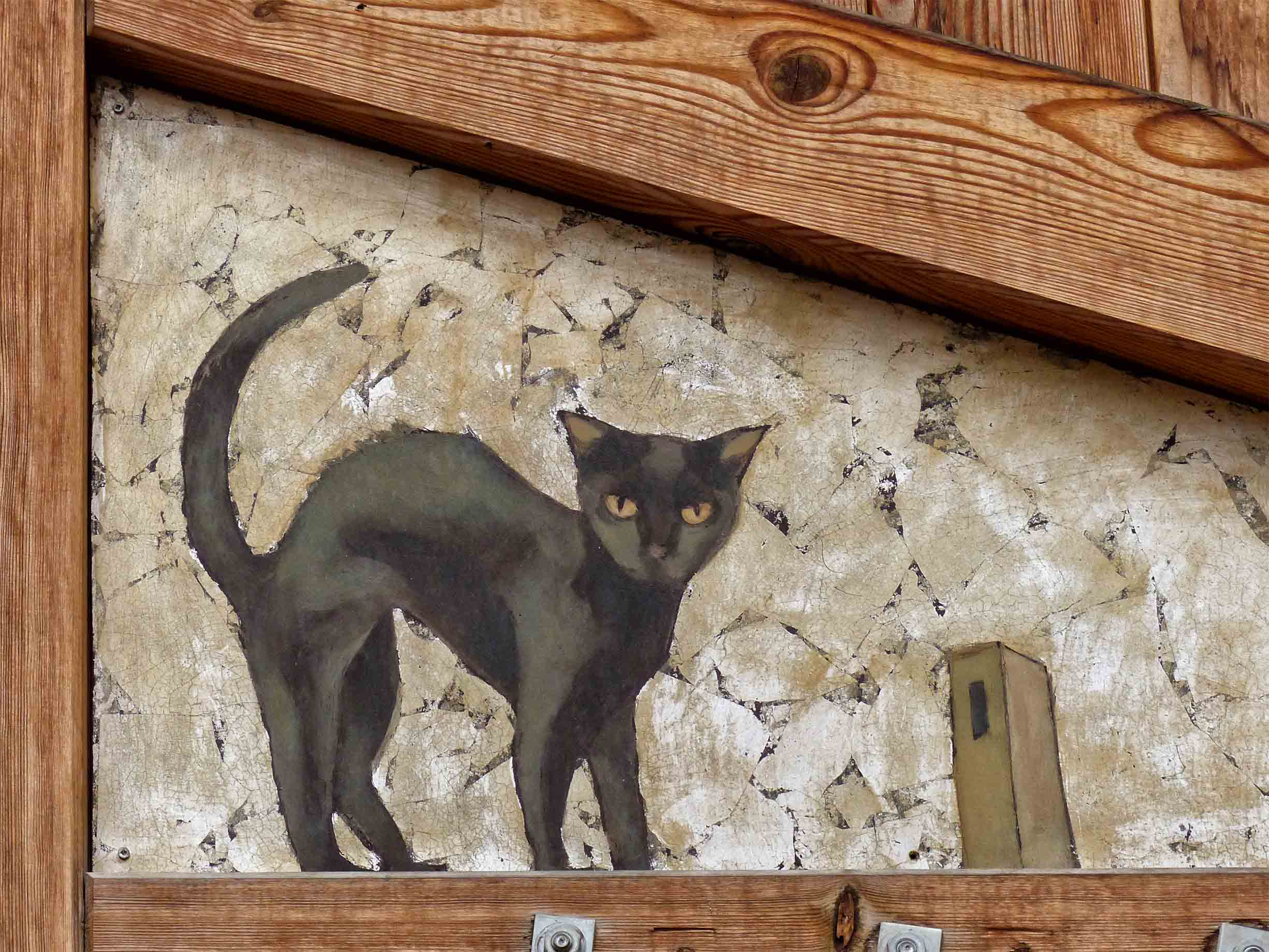 Painting of a black cat on a wall