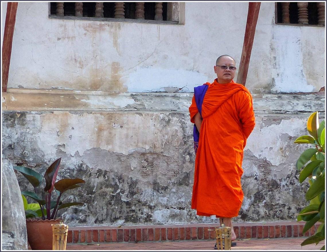 Man in orange robes by worn plaster wall