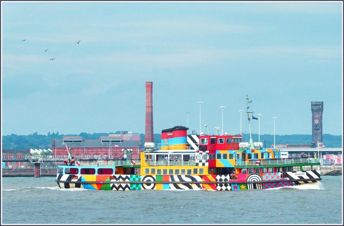 Brightly coloured boat approaching the shore