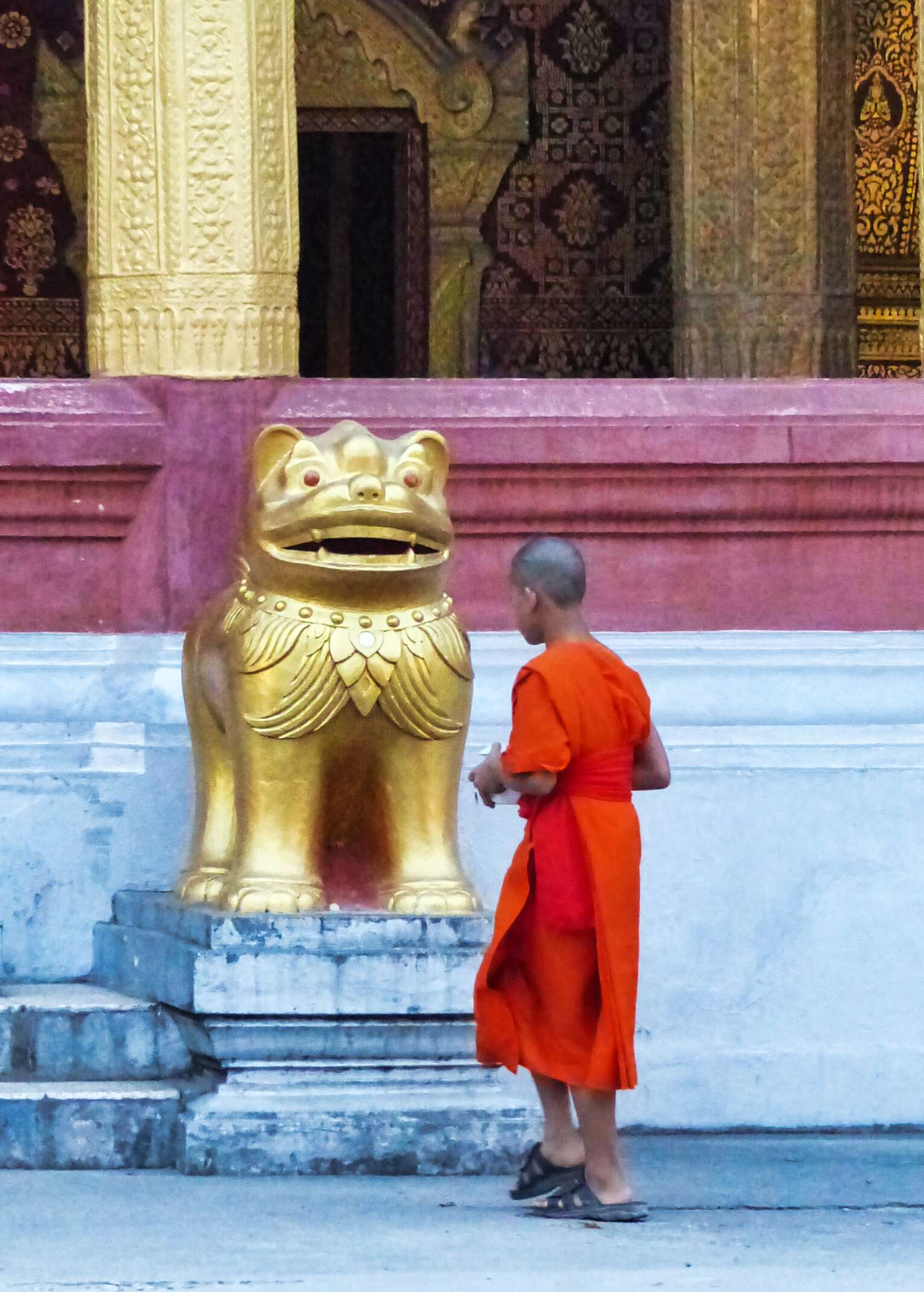 Young man in orange robes in front of a gold lion statue