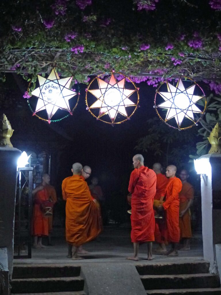 Young men in orange robes talking by the light of lanterns
