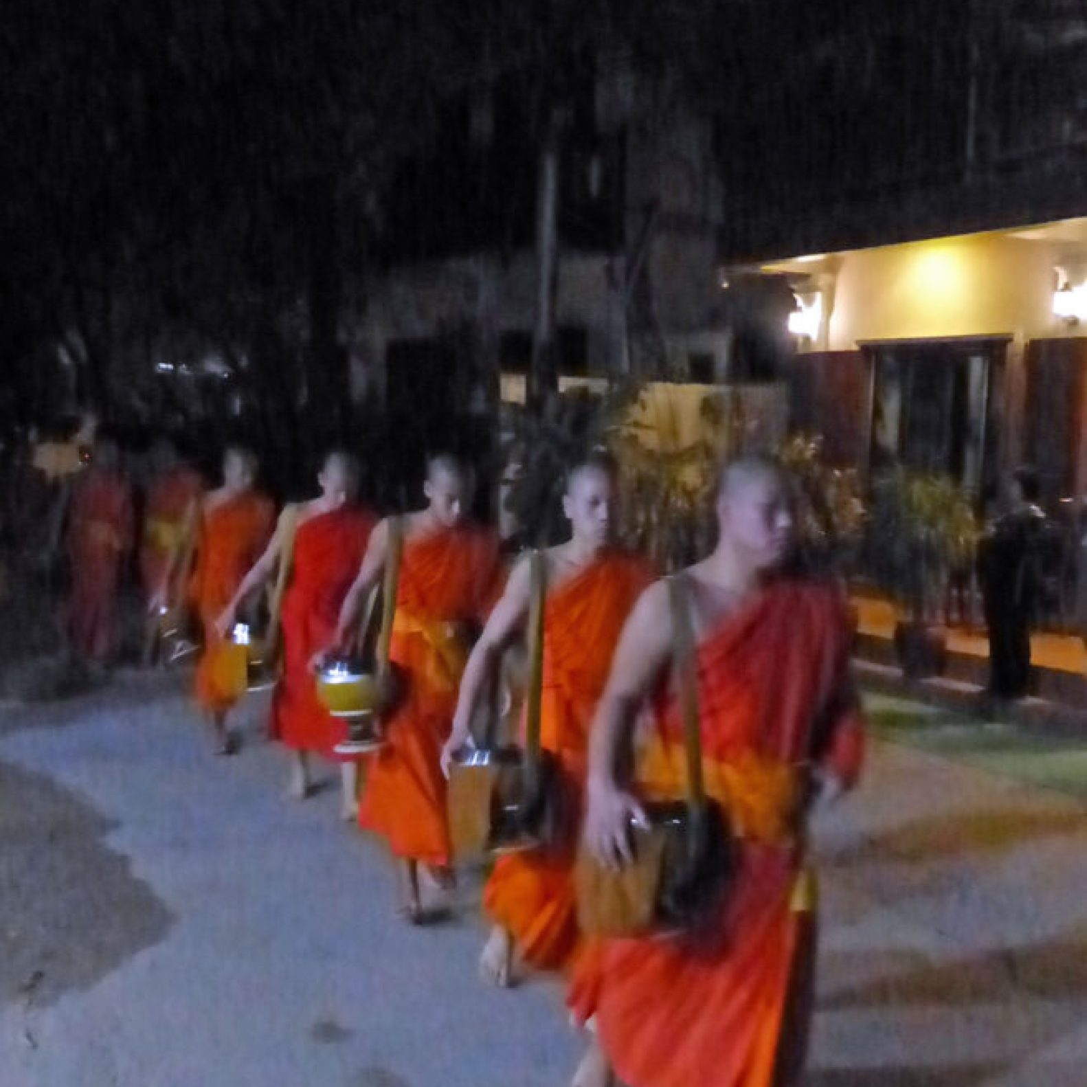 Young men in orange robes walking in single file