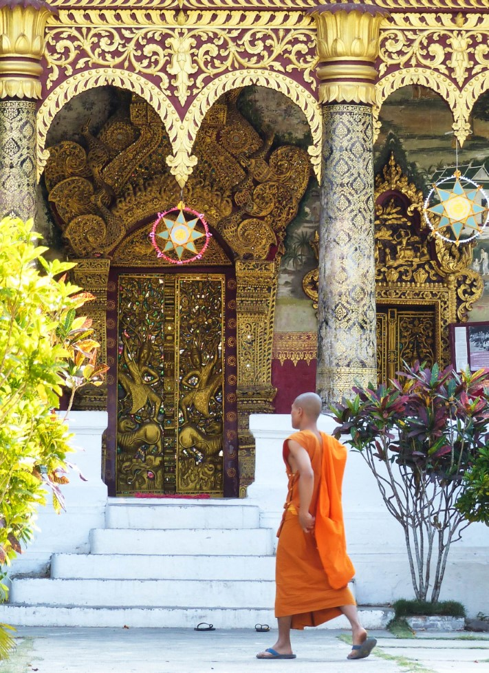 Man in orange robes outside an ornate temple
