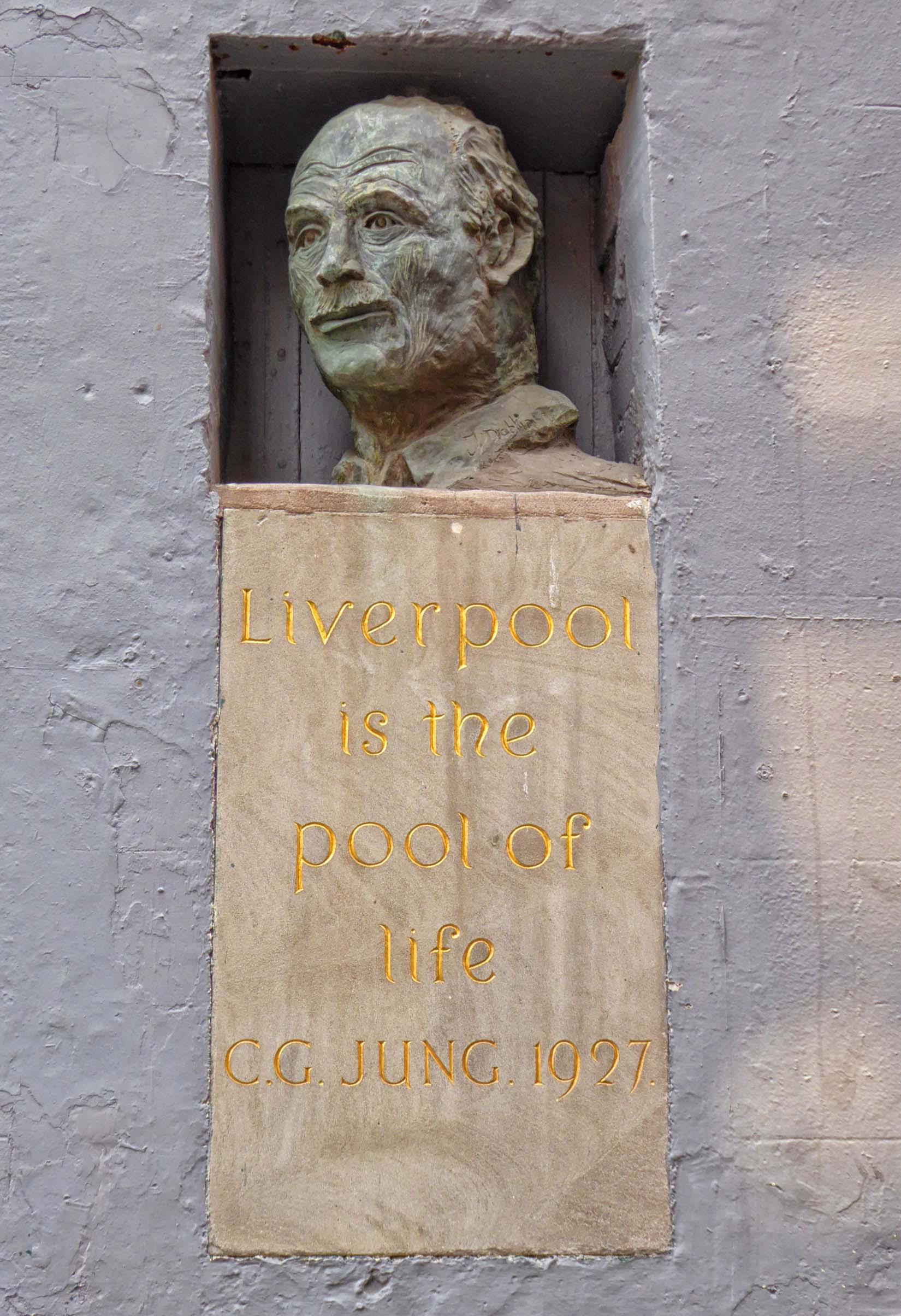 Bust of a man in a niche and text below