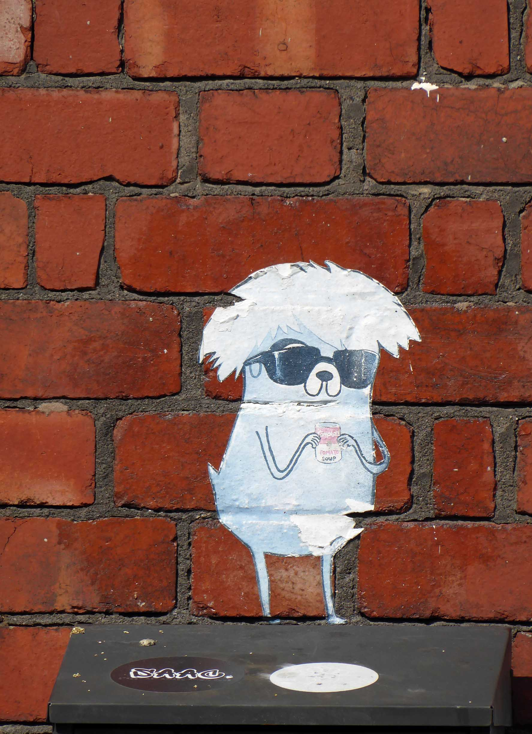 Small painting on bricks of a white creature with sunglasses