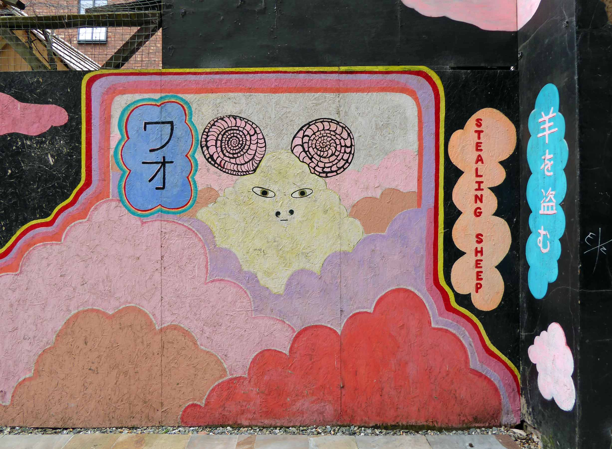 Hoarding with wall painting of clouds and a sheep