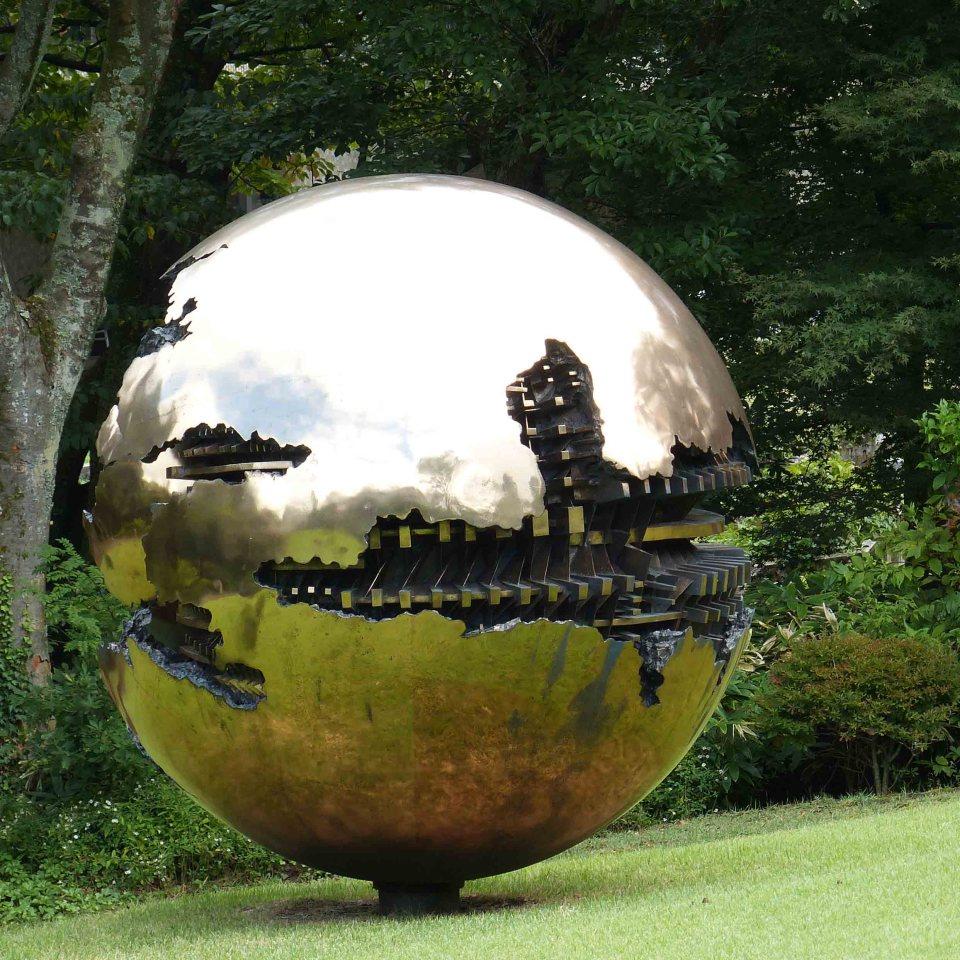 Metal globe sculpture on a lawn