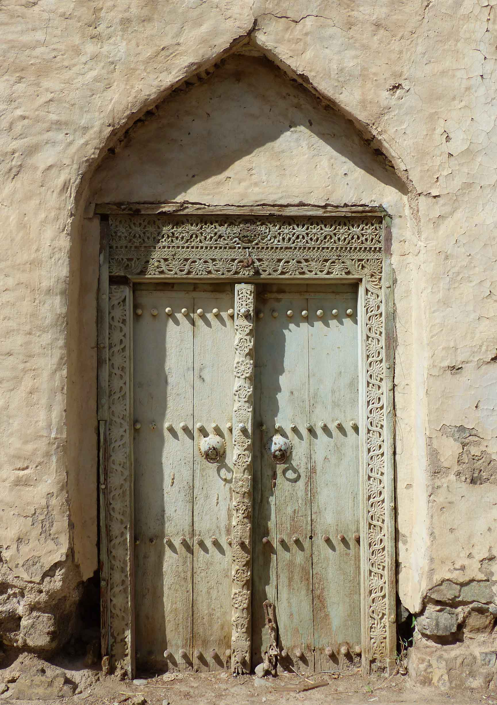 Pale green door with ornate carved frame